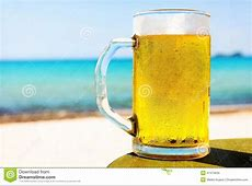 Pint Of Cold Beer On Top Of The Beach Table Stock Photo
