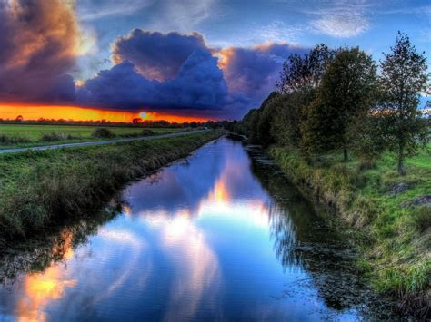 sunset orange sky dark clouds channel water path trees hd