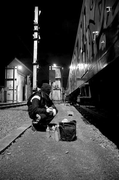 photo   graffiti artist admiring  freight train