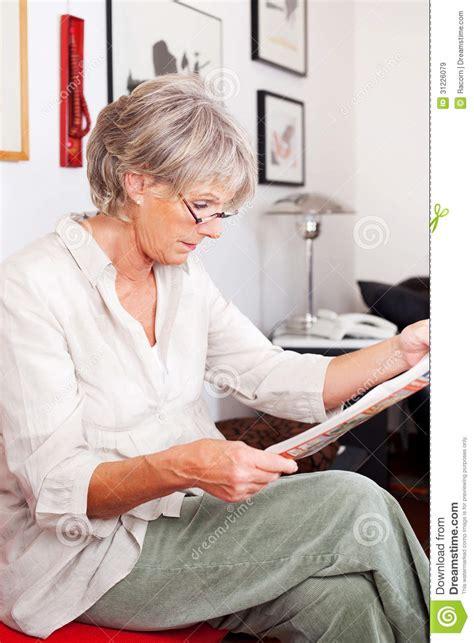 trendy senior woman reading  newspaper royalty  stock