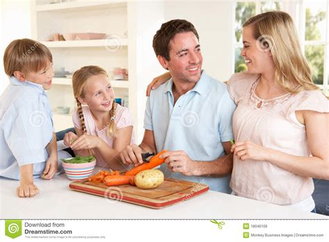 Happy Family Peeling Vegetables In Kitchen Royalty Free