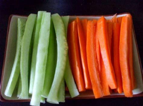 coupe cuisine coupez des batonnets de concombre et de carotte photo de