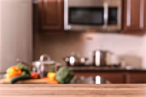 defocused kitchen  empty wooden table foreground stock