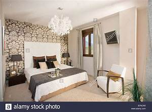 Black and white patterned wallpaper on wall behind bed ...