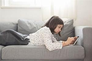 Ragazza Sdraiata Sul Divano E Utilizzando Mini Tablet