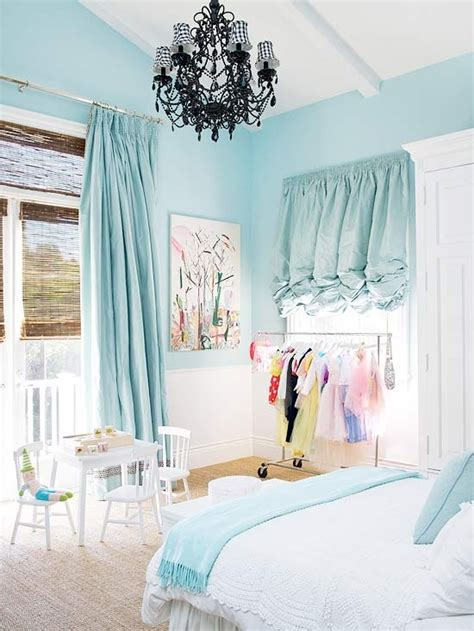 light blue bedroom with black chandelier and ruffle