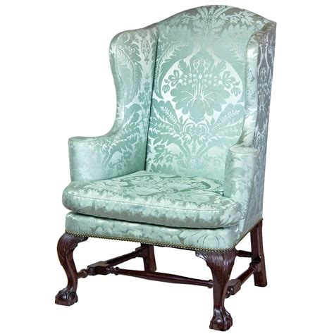 upholstered wing chair with carved knees and claw and