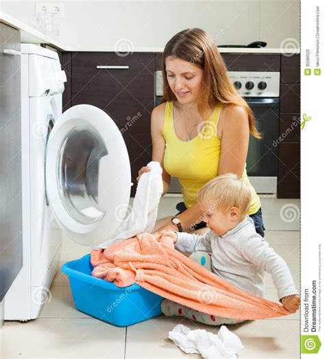 Family Woman Putting Clothes In To Washing Machine Stock