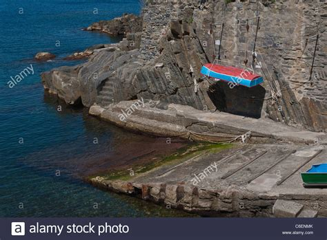 Rock The Boat En Francais by A Small Boat Is Hanging By Ropes From A Rock Cliff By