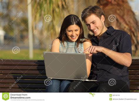 Couple Watching Media In A Laptop Sitting On A Bench Stock