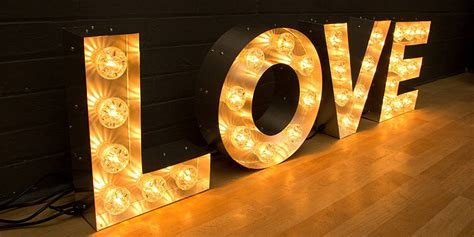 'love' light up fairground bulb sign by goodwin & goodwin