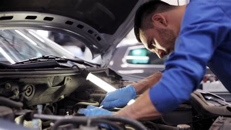 car service repair maintenance and concept mechanic with l working at workshop