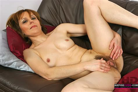 this milf with hairy pussy and small boobs is laying on sofa with open legs to give us close ups