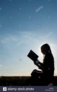 Young Girl Sitting Down Reading A Book At Sunset