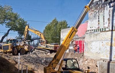 demolition crews remove partially collapsed building