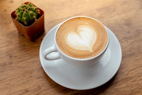 To get this right, you'll need a milk jug with a pointed beak. Coffee latte art heart shape in a white cup on wood table   Premium Photo