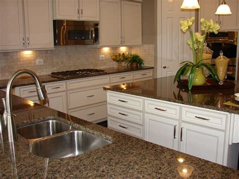 white kitchen cabinets with brown countertops brown granite in a beautiful white kitchen in a model home 2067