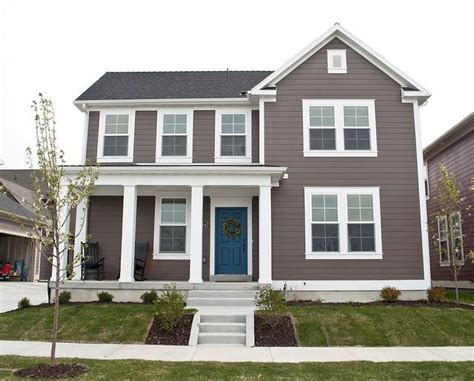 brown house with white trim and blue door photos home in