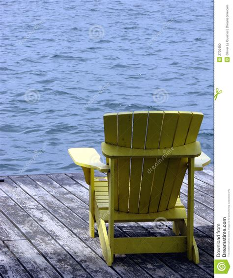 yellow wood adirondack chair on a dock water stock