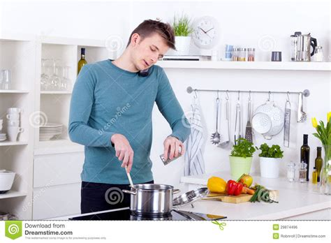young man cooking  meal  talking   phone