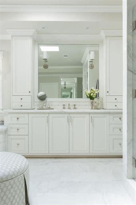 elegant bathroom features white shaker cabinets adorned