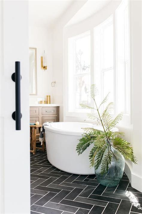 white bay window bathtub  dark gray slate floors