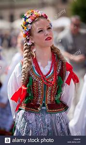 Poland, Cracow. Polish girl in traditional dress preparing ...