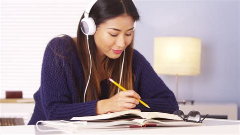 Hundreds of students from around. Chinese Woman Listening To Music While Doing Homework Stock Footage Video 6819847   Shutterstock