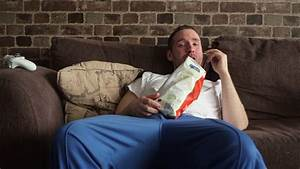 A lazy man sitting on his couch eating potato chips ...