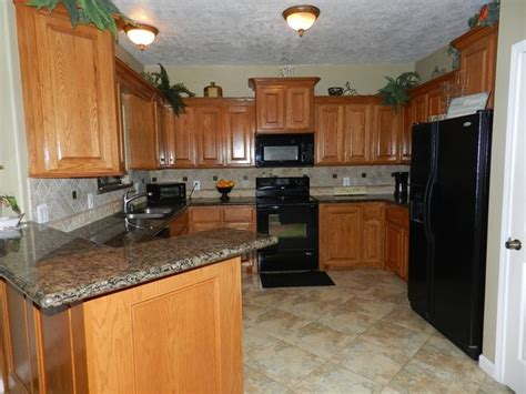 honey oak kitchen cabinets with granite countertops kitchens with oak cabinets with black appliances and