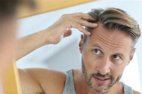 woman checking  hair loss stock image image  dark