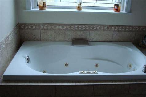 simple travertine border adds elegance   garden tub