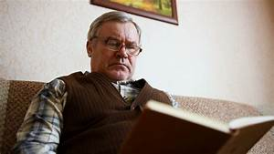 Old man sitting on the couch at home reading a book Stock ...