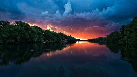 sunset peaceful river coast  green trees forest red