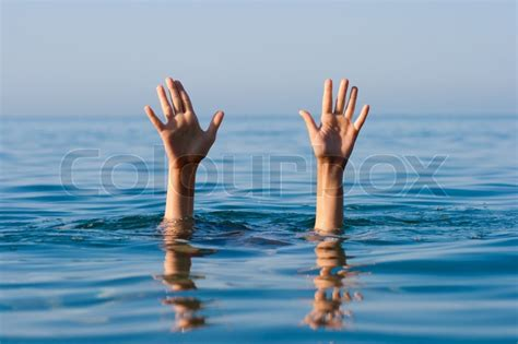 Sink Model by Two Hands Of Drowning Man In Sea Asking For Help Stock