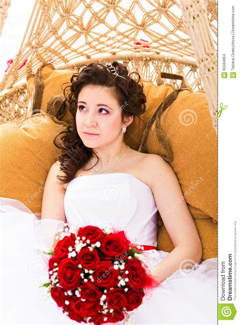Beutiful Bride In White Dress Holding Wedding Bouquet Red