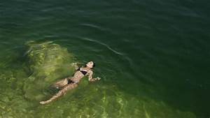 High Angle View Of A Young Woman Dipping Her Feet In Lake ...