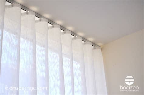 sheer ripple fold curtain on a white curtain track ceiling mounted curtain rail