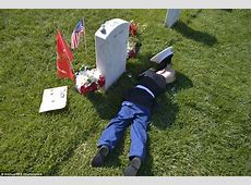 Boy in Marine uniform lies next to his father's grave at