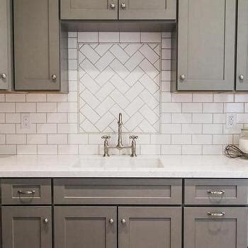 white subway kitchen backsplash in herringbone pattern for