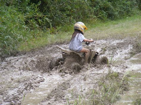 mudding four wheelers family riding in the mud atvconnection com atv
