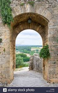 Arched doorway in a medieval stone wall in the Tuscan ...