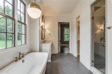 white bathroom  dark gray herringbone tile floor