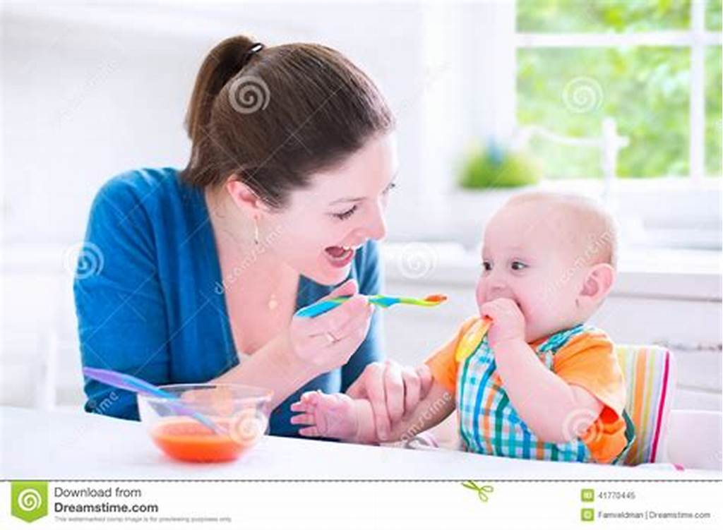 #Baby #Boy #Eating #His #First #Solid #Food #With #His #Mother #Stock