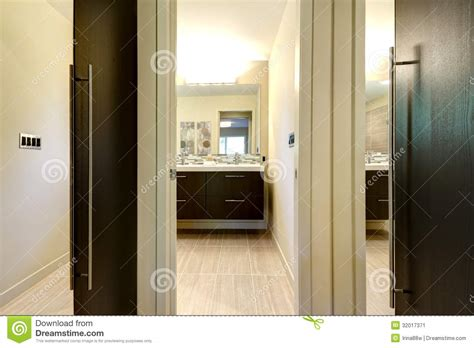 Modern Bathroom With Closet Doors And Hallway With Mirrors