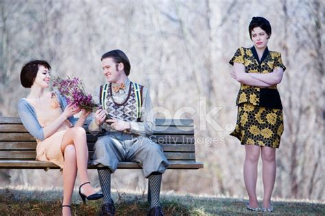 Happy Couple On A Bench While Jealous Lady Watches Stock