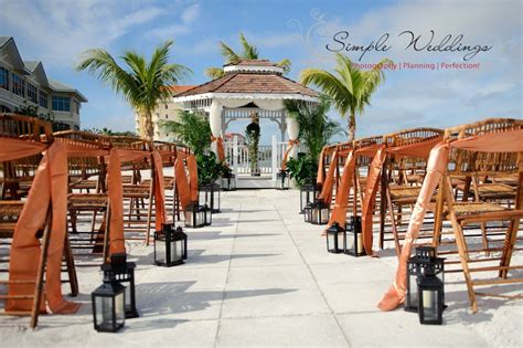 A beach wedding ceremony with bamboo chairs black