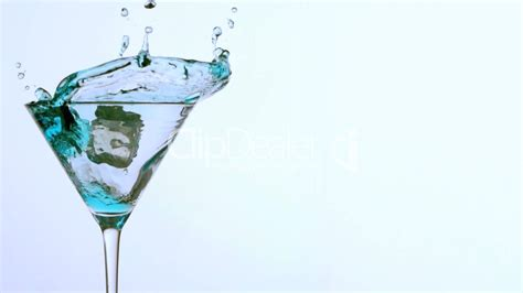 martini glass background ice falling into cocktail glass of blue alcohol on white