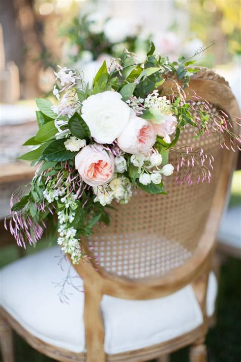 wedding flower and decorated chairs on