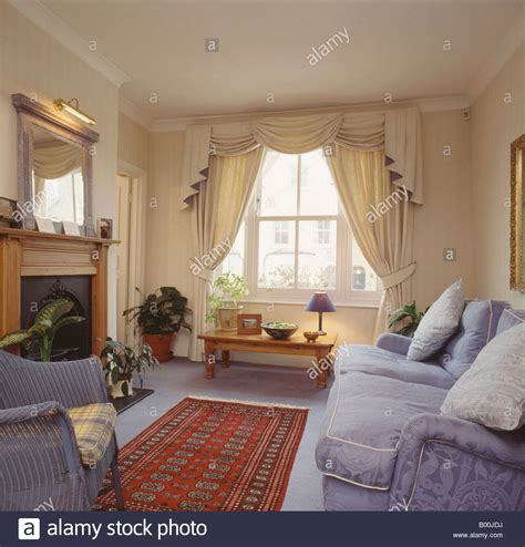 Swagged And Tailed Cream Curtains In Living Room With